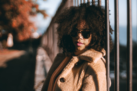The portrait of a young African-American female leaning against an iron fence outdoors in the park; beautiful curly-hair biracial girl in sunglasses in a warm coat outdoors