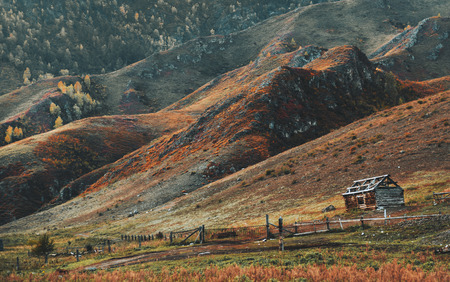 Amazing fall mountain scenery with a small abandoned unfinished wooden shack on the right with an old fence surrounded by vast meadows overgrown with autumn native grasses with hills range behind Stok Fotoğraf