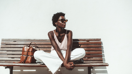A young pensive African female in sunglasses and white trousers is enjoying the summer sun while sitting on the wooden bench outdoors in front of a white wall, with a leather bag next to her Stok Fotoğraf