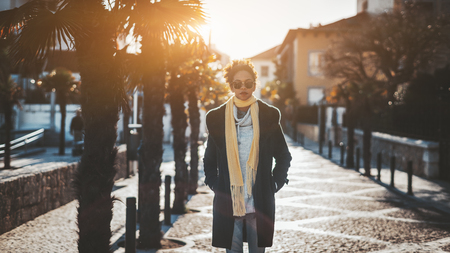 Portrait of a young Brazilian female tourist in a warm demi-season coat and scarf illuminated from behind walking down a narrow street with pavement stone, with palms on the left