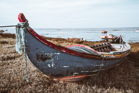 An old peeling colorful wooden rope-bound fishing boat on the grass of the river bank with a horizon,  waterscape and a few other boats behind in a defocused background, Alcochete, Portugal Stok Fotoğraf