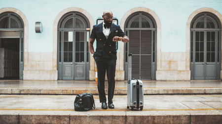 A handsome bald bearded African businessman in a stylish vest and in glasses and with travel bags is looking at his watch while waiting for a train on the railway platform in a railroad station depot