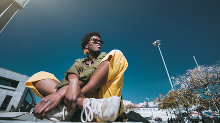 A wide-angle bottom view of a dazzling fashion black girl in sunglasses outdoors on a warm sunny day; a young elegant African female in yellow trousers is sitting cross-legged on the street Stok Fotoğraf