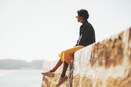 Side view of a young African female with curly Afro hair and earring in the shape of Africa continent sitting on the stone wall near the river, with a copy space zone on the left for your ad message