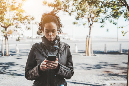 Portrait of a pensive young African-American woman with a smartphone in a warm coat outdoors; a biracial woman is answering an incoming message while standing on the street surrounded by young trees