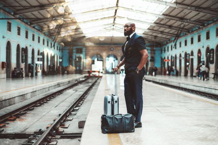 A stylish bald African man entrepreneur with the beard and in eyeglasses and vest, with travel bags is waiting for a train on a railroad platform in a railway station depot to start his business trip