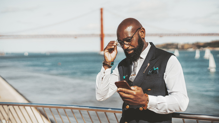 An elegant adult black man entrepreneur is looking at the screen of his smartphone and adjusting spectacles while standing outdoors near the river with a suspension bridge in a defocused background