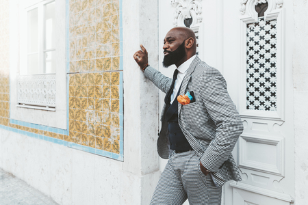 An elegant bald African senior with the beard and in a checkered suit, near the wooden door is leaning against the wall tiled with traditional Portuguese tiles Azulejo and pensively looking straight Stok Fotoğraf