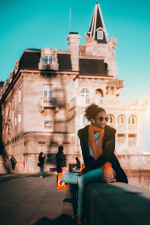 Young beautiful African-American female tourist is resting on a stone fence with an antique building behind; a vertical shot a biracial curly-hair girl in sunglasses sitting on the stone curb outdoors Stok Fotoğraf