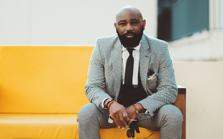 A serious adult bearded bald African man in an elegant plaid costume with a tie is sitting on a yellow soft sofa outdoors and looking at the camera with round spectacles in his hand