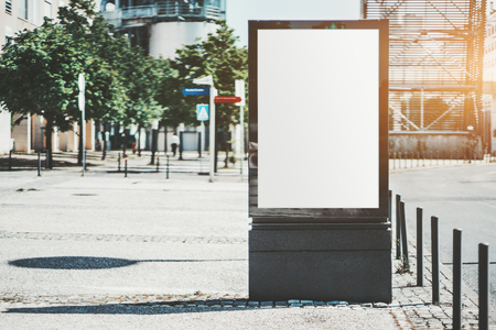 Mockup of a blank information poster in urban settings near the road turn; an empty vertical street banner template on the sidewalk; an outdoor billboard placeholder mock-up on the pavement, sunny day