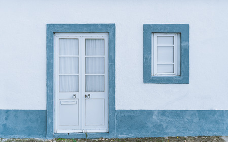 View of an antique verandah outdoors with a small window and the door on a white wall with light-blue strokes, there is a hole in the door for mail, behind the glass there is a tulle, Portugal
