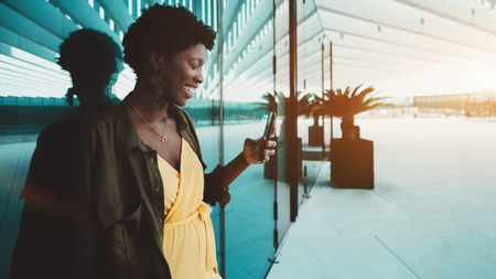 Laughing black girl having an online video call with her friend via smartphone near the glass wall; cheerful young African female entrepreneur answering message on her cellphone near office entrance Stok Fotoğraf