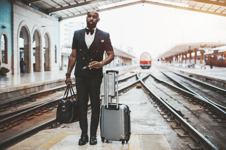 An adult bald bearded elegant African man entrepreneur with travel bags and spectacles in his hands on a railway platform with track junctions behind and a red locomotive, copy space area on the right Stok Fotoğraf