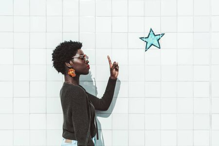 Side view of a charming young African woman in sunglasses wagging her finger at a painted star above her head as a symbol of an idea that came to mind; a black girl is pointing up with her forefinger Stok Fotoğraf