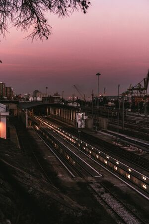 Vertical view of a modern railway depot during a lilac sunset in the dusk, with most of railroad tracks empty, with sequences of lights stretching into a hangar; port and dock area in the background