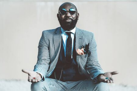 A concept photo with an elegant bald bearded black man in a suit with tie and round sunglasses from the matrix offering to make a choice with red and blue pills in his hands Stok Fotoğraf