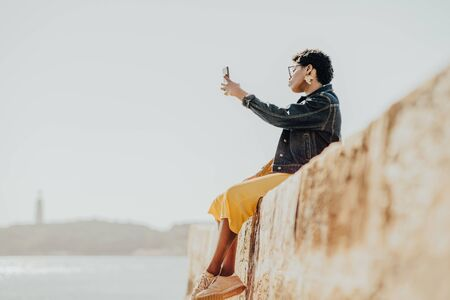 View of a young African female in yellow trousers and denim black jacket, in sunglasses and with earrings in shape of Africa continent, sitting on a wall near river and taking a selfie via a cellphone Stok Fotoğraf
