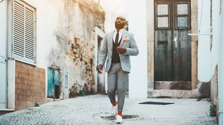 An elegant bald bearded African man in a fashion costume with tie and orange socks is walking down the antique street of a European city; a fancy black guy in a suit is leaving the door of his house