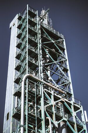 A vertical view from the ground of a contemporary oil refinery building or a fuel factory facility in an industrial zone, with plenty of pipes, metal beams, and stairs; elevator on the left Stok Fotoğraf