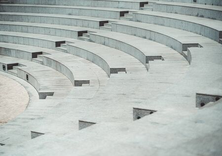 Rows of grayish stony or marble seats and flights of stairs of a modern outdoor amphitheater with a pavement stone on the stage down below