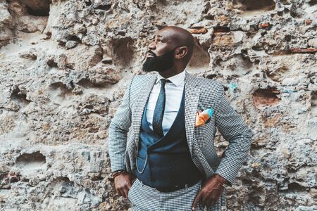 Handsome bald bearded black senior in an elegant costume in front of a grungy wall outdoors; a fashion adult African man with the beard and in a suit with vest and necktie standing near a stone wall