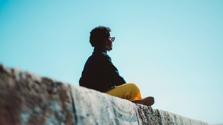 Rear view of a Buddhist African female sitting on the stone wall and praying; view from behind of a black girl in a denim jacket and yellow trousers enjoying the sun while sitting on a stone surface