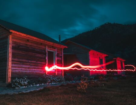 A long exposure night scene with multiple tiny huts in on a camp site in Altai mountains with a hill ridge in the background and a glowing stroke of a red light starting in the foreground