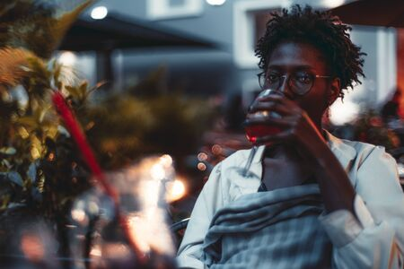 A charming tired black woman in spectacles is sitting at the table on the terrace of the summer cafe and drinking delicious sangria cocktail in the dark, with a copy space place on the left Archivio Fotografico