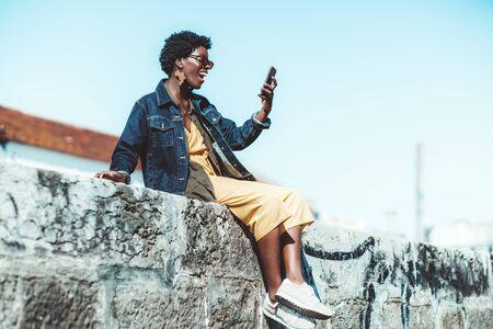 Una mujer africana riendo feliz con una chaqueta de mezclilla está teniendo una videollamada a través de su teléfono inteligente con su amiga mientras está sentada al aire libre en una pared de piedra en un día soleado, con un área de espacio de copia a la derecha
