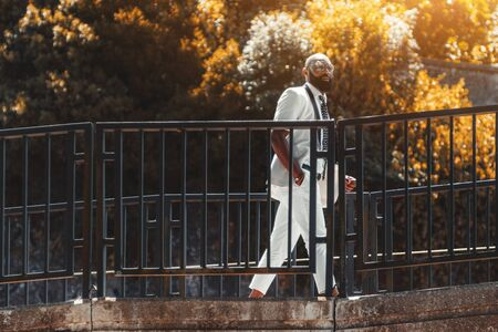 An elegant African man in a white fashion suit and spectacles is crossing the bridge outdoors; a fancy black guy in eyeglasses is walking on the overhead passage on a sunny day