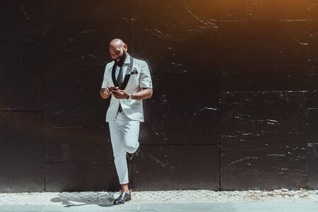An elegant bald African senior with a heavy beard and in a white fashion costume is leaning against a black glossy textured wall, smiling, and using his cellphone, with a copy space place on the right 写真素材
