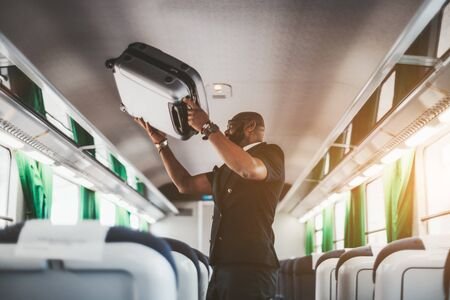 An adult fancy bald African businessman in a vest and eyeglasses is putting luggage on the shelf while standing in the middle of a first-class carriage of a high-speed train during his business trip