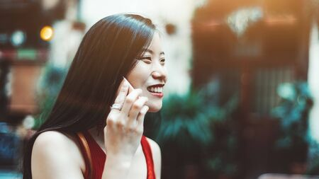 A dazzling young Asian woman with long hair is talking on the smartphone outdoors on a warm sunny day, with a copy space place on the right for an advertising message or your logo