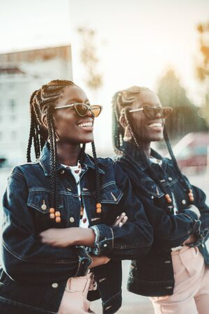 A dazzling happy young black female with braids and in a denim jacket and sunglasses is leaning against the mirror wall outdoors and smiling; a charming African girl laughing on the street