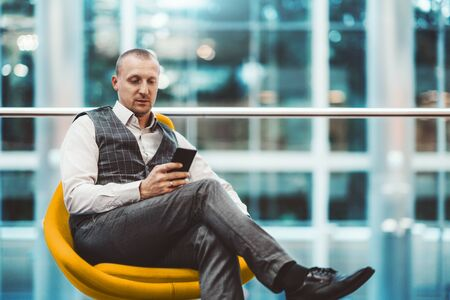A confident adult man entrepreneur is sitting on an orange soft armchair in a modern office settings and using his smartphone; a caucasian businessman with the cellphone indoors, defocused background 스톡 콘텐츠
