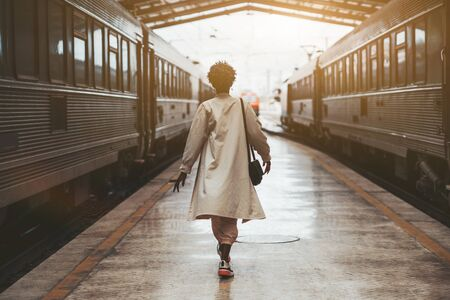 Rear view of a walking African woman in a white cloak on the railway station before her trip between two highway trains waiting for departure on the platform indoors of a railroad depot