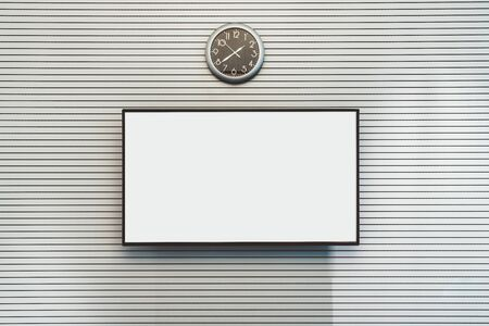 The mockup of a big empty LCD screen hanging on a striped wall of an office meeting room with a watch above; the template of a blank plasma TV screen on the white surface with lines and a wall clock Фото со стока