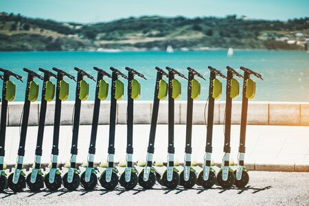 Urban electric transportation outdoors: an unfinished row of slightly shabby electric scooter bikes with green batteries blocks on the top, embankment of Lisbon, Portugal, with the Tagus river behind