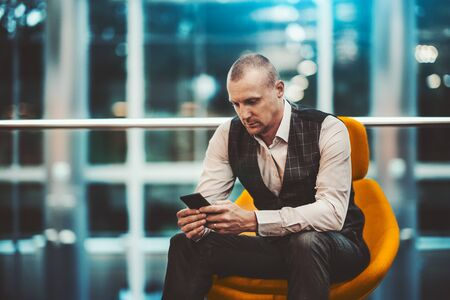 A pensive adult man entrepreneur is sitting on an orange soft armchair in modern office settings and using his cellphone to send a message; a caucasian businessman with the smartphone indoors