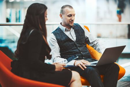 An adult man entrepreneur in a checkered vest is sitting on a curved orange armchair and showing his female colleague a business plan using a laptop with an interface hologram in front of the screen 스톡 콘텐츠