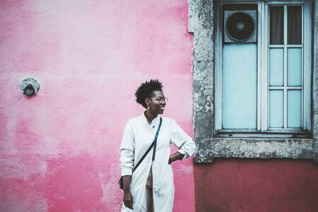 An elegant cheerful young black girl in a white cloak and eyeglasses is smiling and looking aside while standing in front of an old wall with a window and the plastering painted into pink color Stock fotó