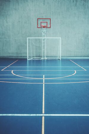 Front view of the court in the gym hall; indoors modern contemporary office stadium with a basketball basket and hoop, football goal, colored marking on the floor, a concrete wall in the background