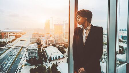 A pensive African-American woman entrepreneur is thoughtfully looking at the cityscape outside the window while leaning on the window frame on the top floor of a luxury business office interior
