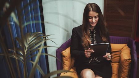 Young businesswoman is sitting on a modern armchair with green cushions and reading incoming email using digital tablet; a caucasian woman entrepreneur is using her tablet pc in a lounge office area