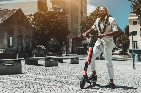 A fancy adult bearded bald African guy in a spectacles and a white suit is holding in his hands the handlebars of the e-scooter ready to ride; a copy space place on the left for your logo or a text Stockfoto
