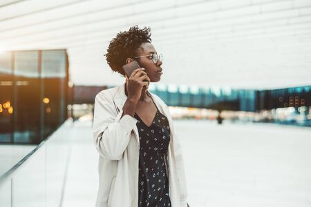 A charming young African woman entrepreneur in a white cloak and spectacles is having a business conversation using a smartphone while standing in an outdoor entrance of a contemporary office building
