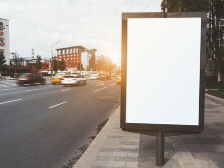 Mockup of a blank narrow info poster in urban settings, long exposure shot; an empty vertical street banner template on a sidewalk; an outdoor billboard placeholder mock-up near a road with cars