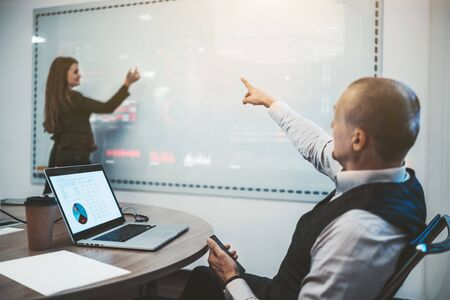 A caucasian man entrepreneur is pointing with his hand on a white projection board to his female business colleague to fix a chart and data on the screen; selective focus on the laptop and his hand