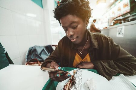 A charming young African female is making a pause in her lunch in an eatery to answer a message on a smartphone; a cute black girl is scrolling news feed on a cellphone while sitting in a kebab house